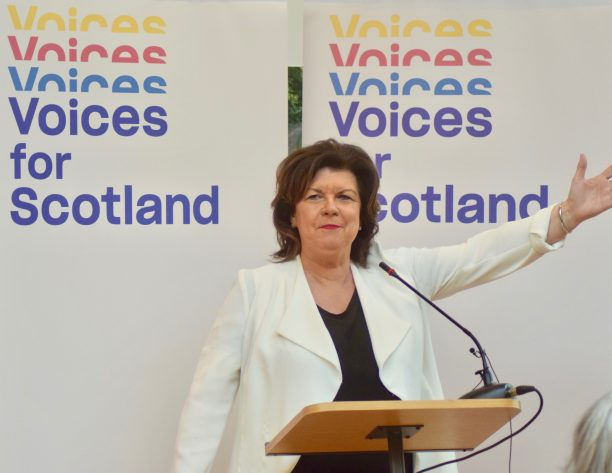 Elaine C Smith standing in front of Voices for Scotland banners