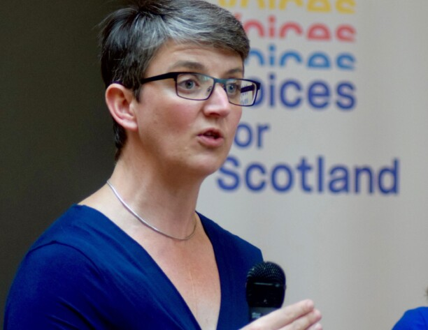 Maggie speaking in front of a Voices for Scotland banner