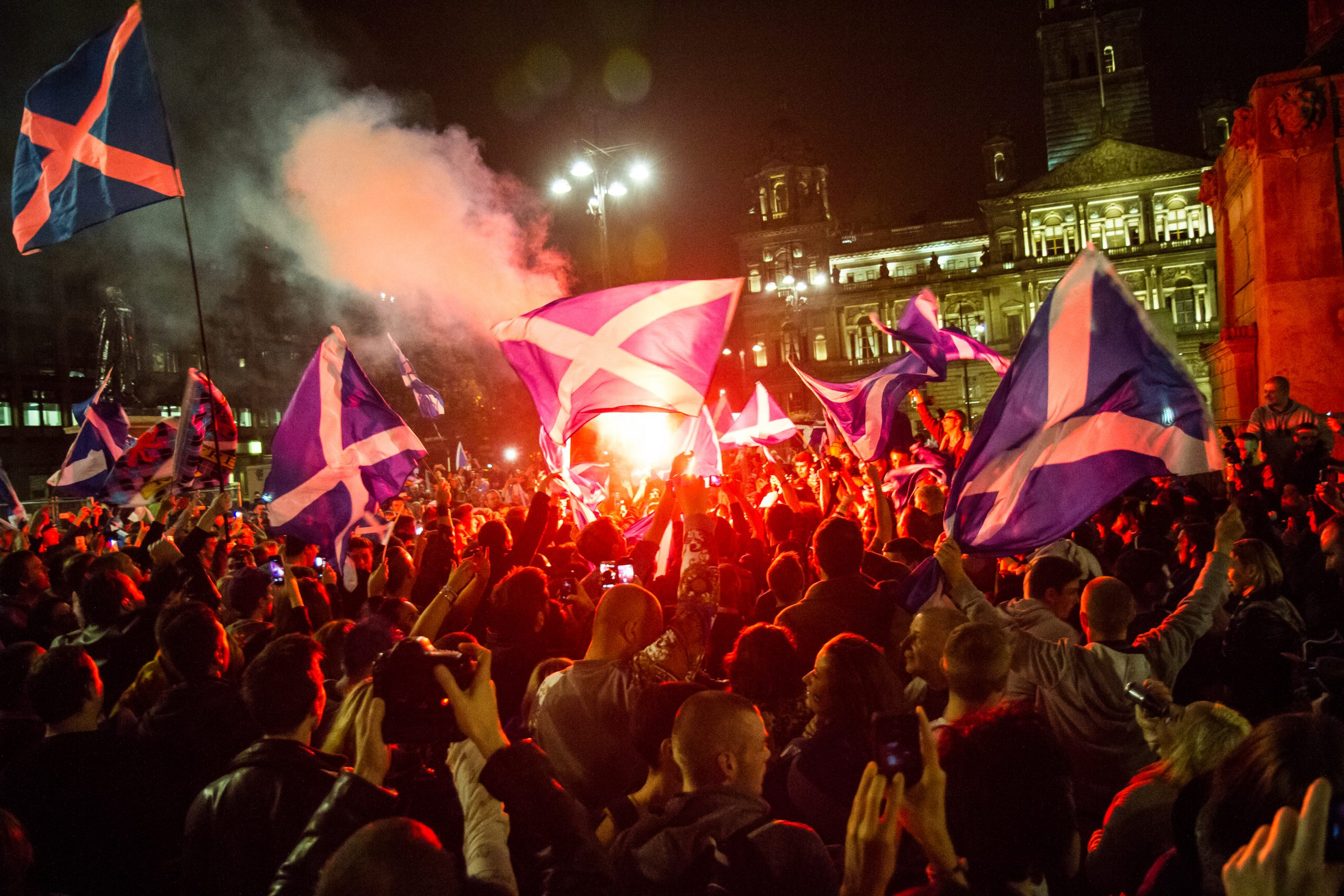A crowd with Scotland flags at night in George Square Glasgow